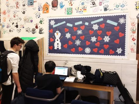 Two Uni students sitting next to snowflake-covered bulletin board