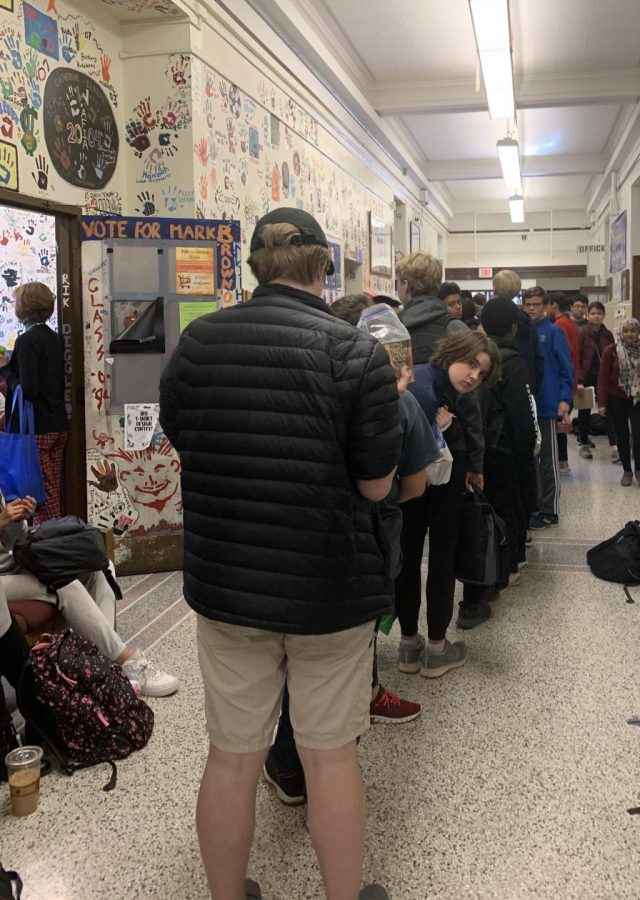 Students lining up with cans of food for the Thanksgiving food sale